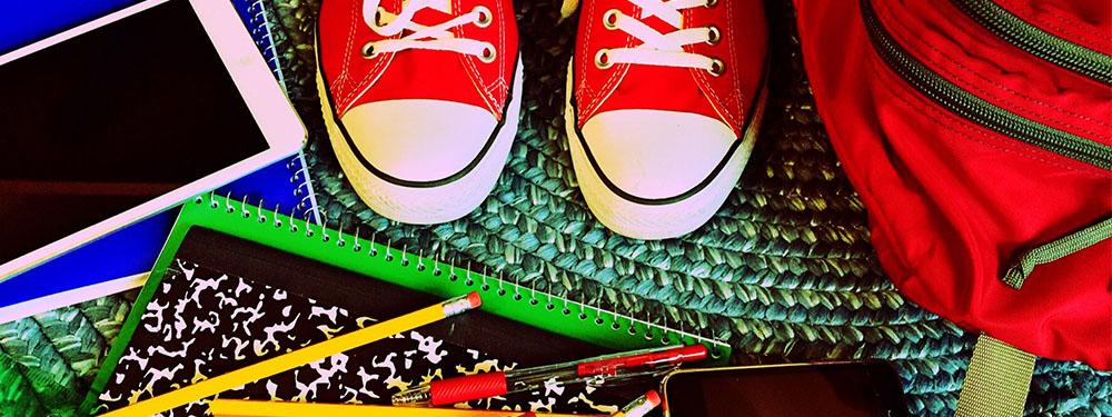 Photo prise d'en haut montrant des converses rouges avec au sol cartable, crayons, cahier et téléphone portable