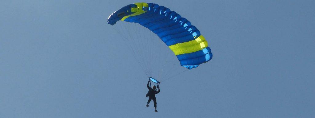 visuel d'un homme sautant en parachute bleu et jaune
