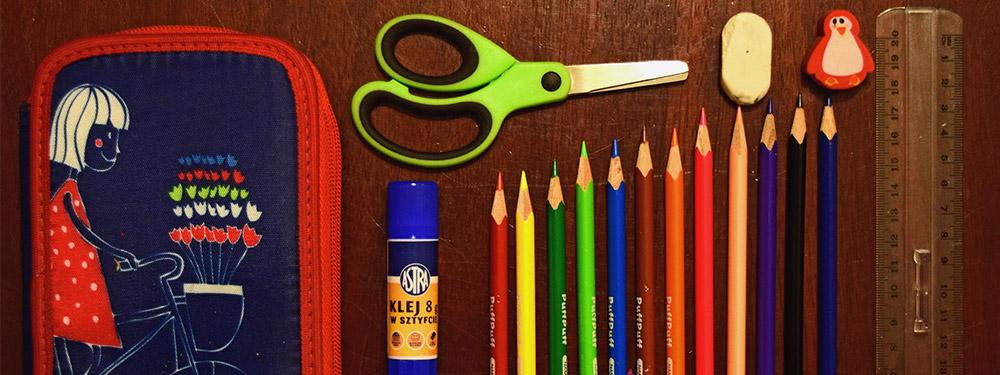 Photo de fournitures scolaires jonchés sur une table en bois : trousse, ciseaux, colle, crayons de couleurs, gomme et règle