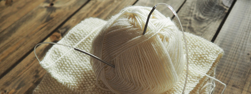 Photo d'un projet d'écharpe tricotée avec une pelote de laine blanche posée sur le dessus joinché sur le sol