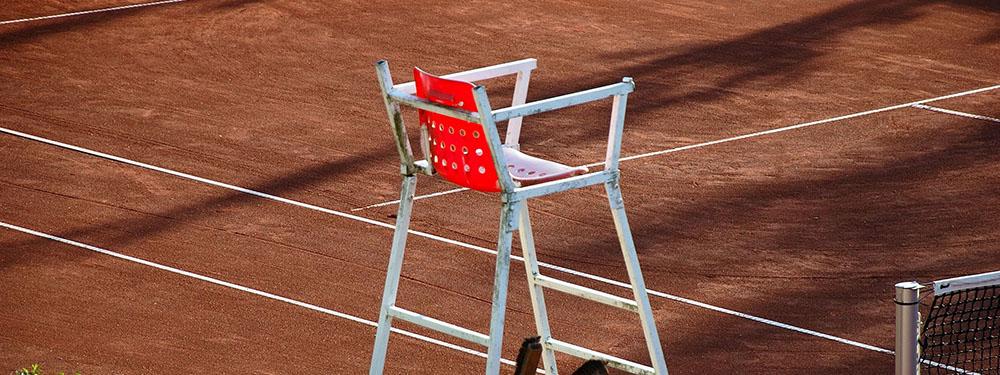 Photo d'un fauteuil d'arbitre vide sur un terrain de tennis en terre battue
