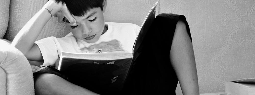 Photo d'un enfant assis sur un canapé en train de lire un livre