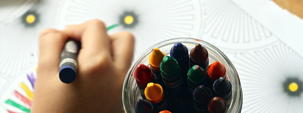 Photo d'une main d'enfant en train de colorier des mandalas son pot de crayons pas loin