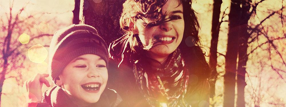 Photo d'une femme et de son fils entourés d'arbres en train de rire avec un filtre vintage