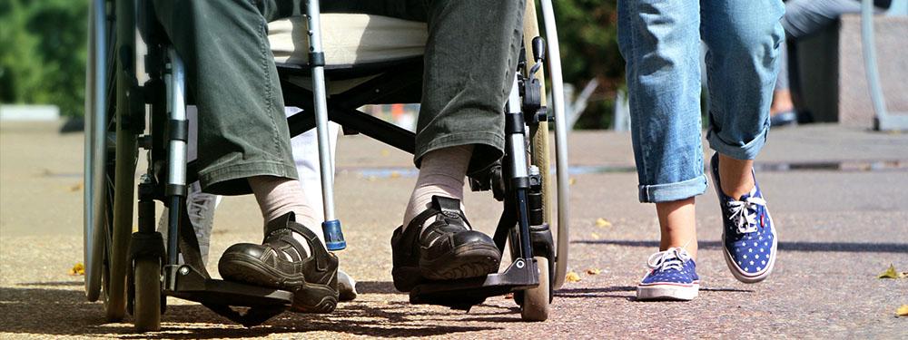 Photo d'un homme en fauteuil roulant avec une jeune fille marchant à ses côtés
