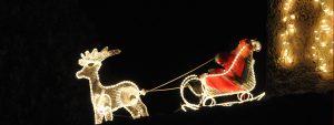 Photo du père Noel dans un traineau tiré par un rene lumineux pour marquer les illuminations de noel
