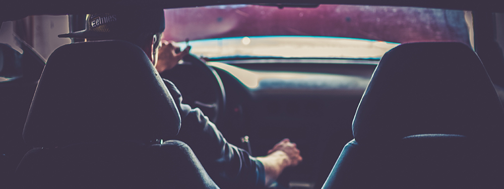 Photo d'un jeune homme vu de dos au volant d'une voiture