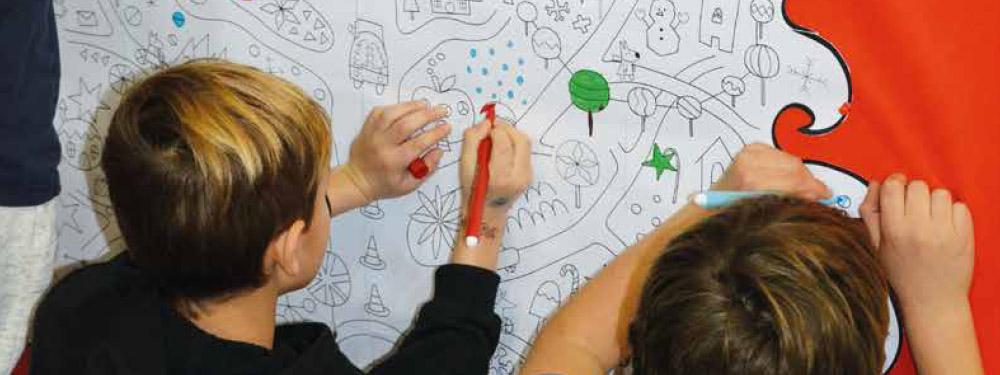 Photo de 2 enfants de dos en train de colorier une dessin sur un mur