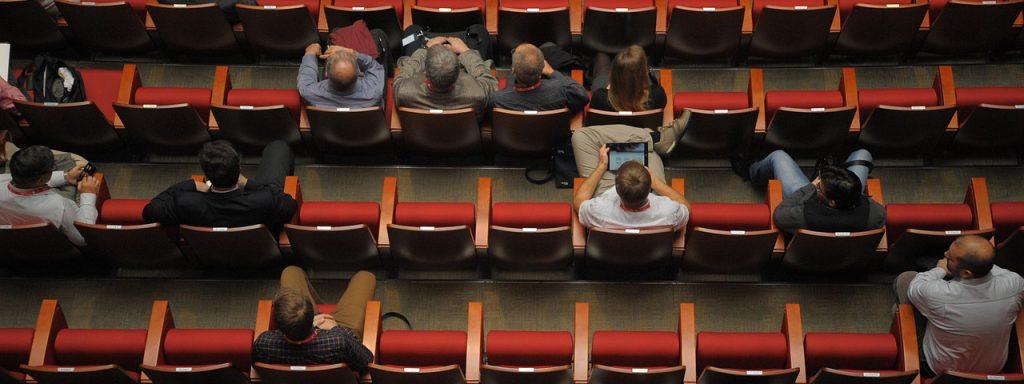 Visuel de personnes assises dans une salle de conférence