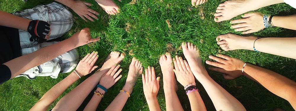 Photo de mains et de pieds de jeunes positionnés en cercle sur du gazon