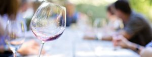 Photo d'un verre de vin en gros plan avec en fond et en flouté des gens attablés tenant eux aussi un verre pour une dégustation