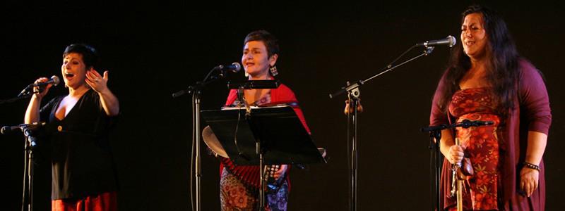 photo de 3 femmes qui chantent au micro
