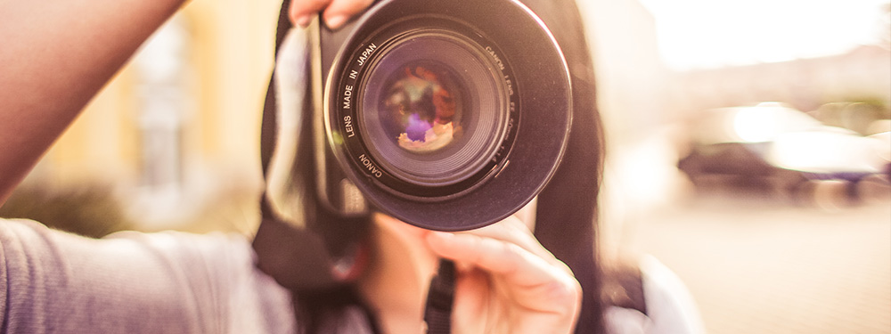 Photo d'une femme derrière un objectif en train de prendre une photo
