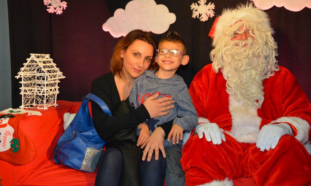 Photo d'une maman et son enfant posant à côté du Père Noel