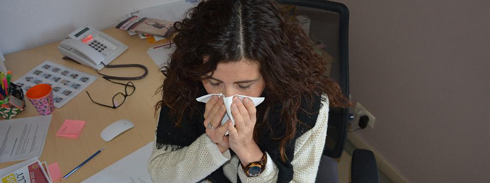 Photo d'une femme installée à son bureau en train de se moucher