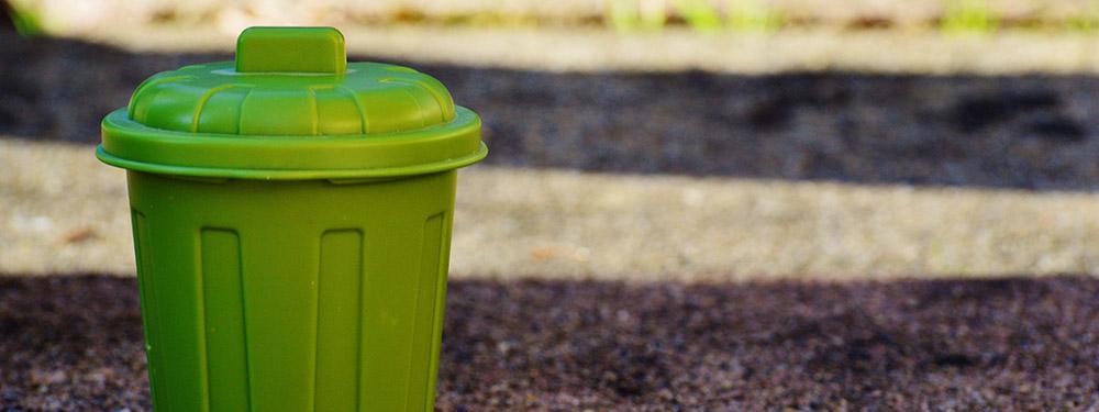 Photo d'une poubelle verte posée sur un trottoir