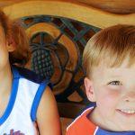 Photo de 2 enfants, assis sur un banc, tout sourire en tenue de sports