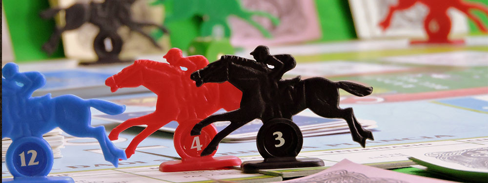 Photo zoomée de 3 pions représentant des cavaliers sur des chevaux sur un plateau de jeu de société