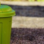 Photo d'une poubelle verte sur un trottoir