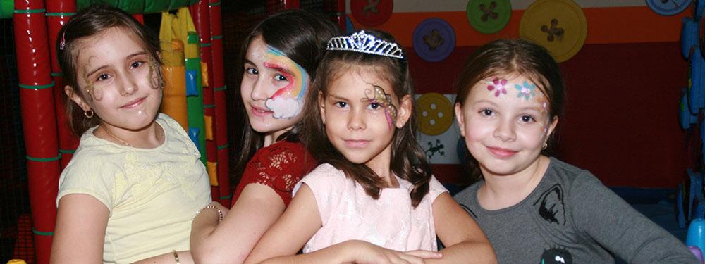 Photo de 4 fillettes maquillées avec des fleurs, papillons, arc-en-ciel sur le visage prenant la pose