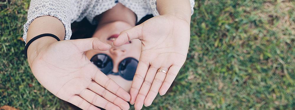 Photo d'une femme allongée dans l'herbe avec les mains formant un coeur