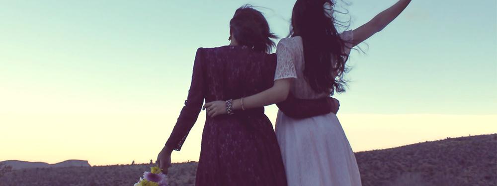 Photo de 2 femmes de dos se tenant par la taille dans un décor montagneux