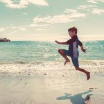 Photo d'un enfant en combinaison de plongée sautant sur une plage