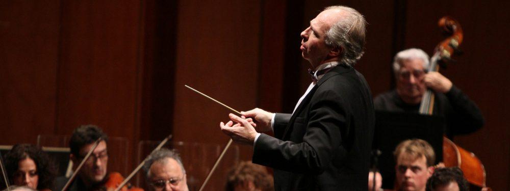 Un chef d'orchestre, baguette levée, conduit les musiciens de l'orchestre
