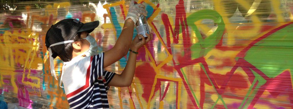 Photos représentant un petit garçon en train de faire un graff aux couleurs vives : rouge, jaune et vert
