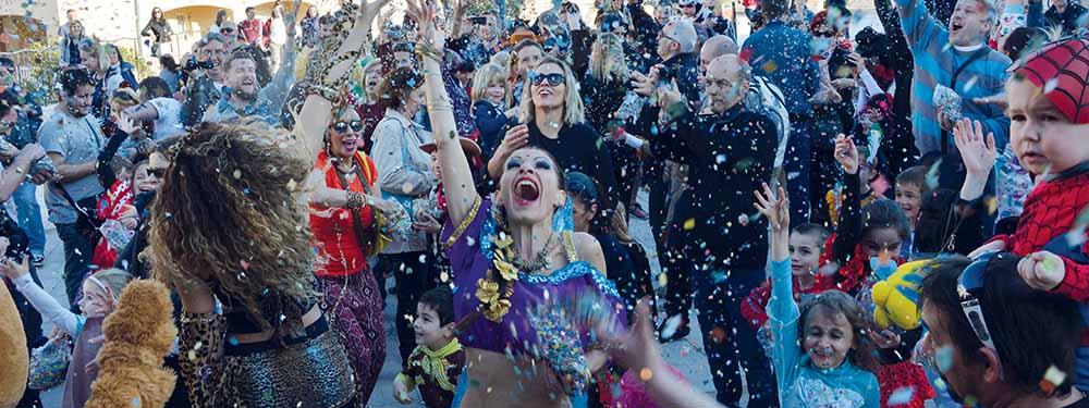 Photo du carnaval montrant la foule et une danseuse tout sourire lançant des confettis en l'air