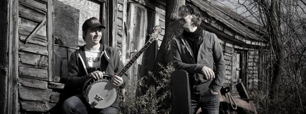 Photo du Groupe Dans l'shed posant devant une maison en bois instrument à la main