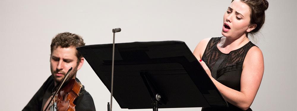 Photo de Emismena chantant au côté d'un violoniste