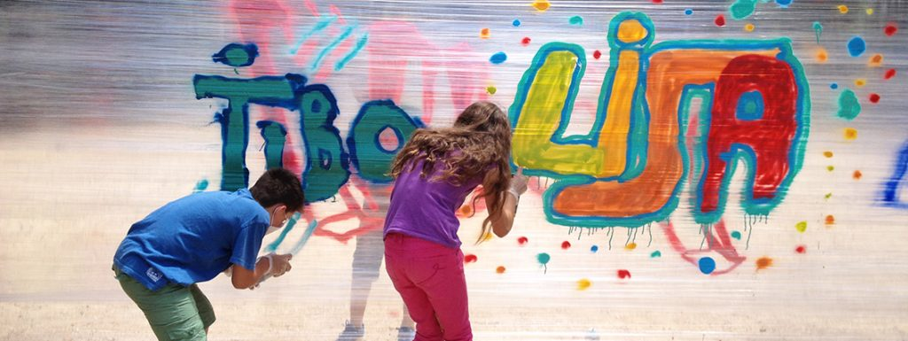 Photo représentant deux enfants en train de graffer leurs prénoms sur cellophane : Tibo et Lisa