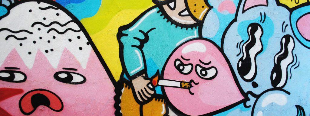 Graffiti représentant des personnages en chewing gum roses et bleues. Le personnage central fume une cigarette.