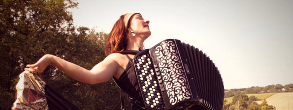 Photo de Ludivine Hedocq dansant dans un champs avec un accordéon dans les bras