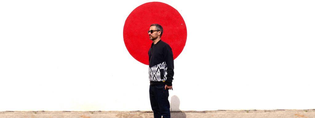 Photo representant un homme de profil devant un mur blanc avec en son centre un rond rouge