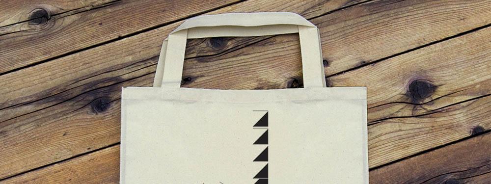 Photo d'un tote bag posé sur un sol en bois