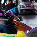 Photo de 2 parents accompagnant leurs enfants dans des auto tamponneuses