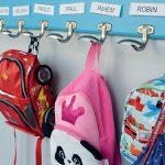 Photo de cartables accrochés sur des porte-manteaux mentionnant le nom des enfants : Sacha, Romain, robin, Paul, Melissa…