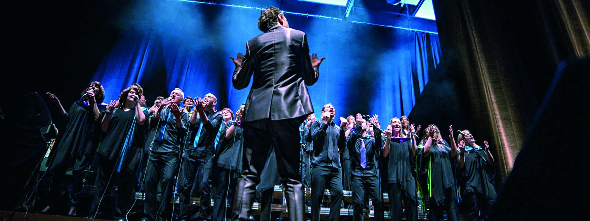 Photo représentant Le Massilia Sounds Gospel en train de chanter mené par le chef de choeur Greg Richard