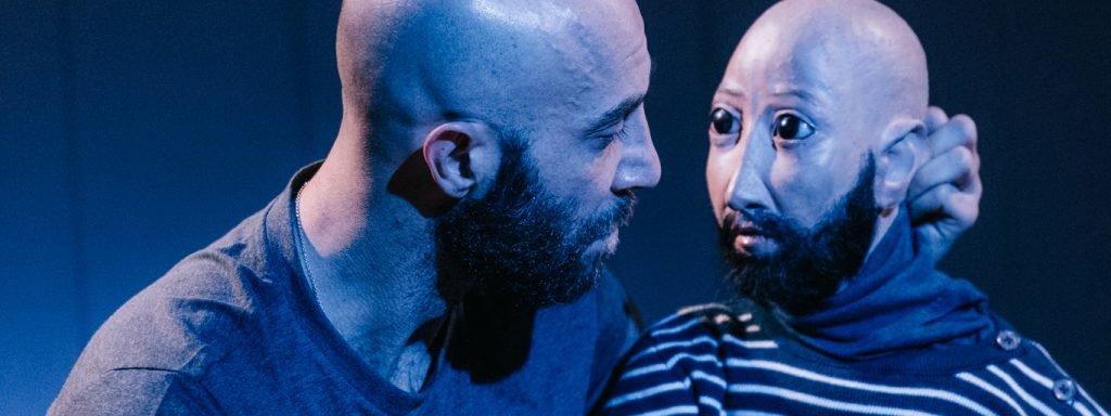 Photo représentant un personnage dans la pénombre dialoguant avec son double en marionnette