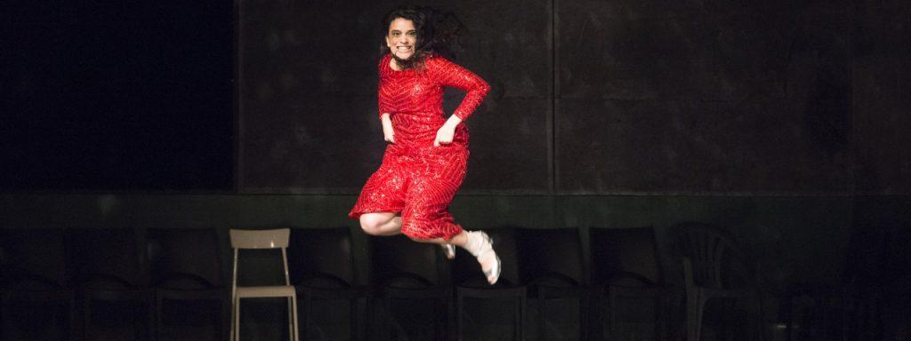 Photo représentant une femme vêtue d'une robe rouge à paillettes en train de sauter de joie sur une scène
