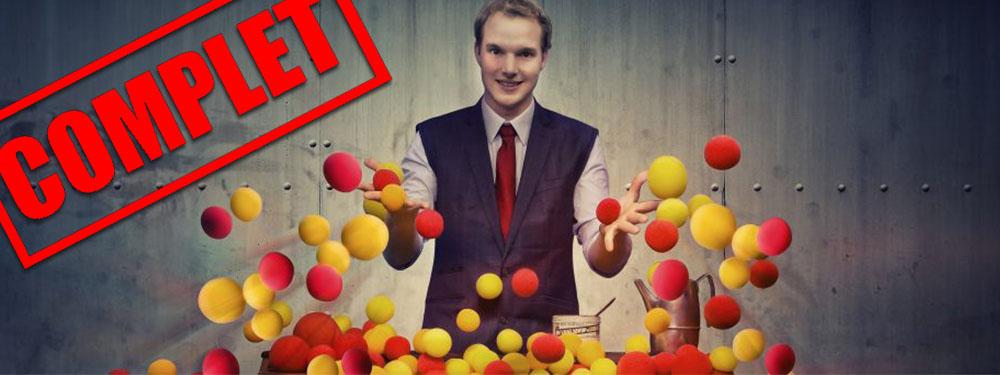 Photo représentant un magicien jouant avec des balles rouges et jaunes