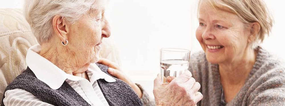 Photo d'une femme donnant un verre d'eau à une femme senior assise sur un canapé