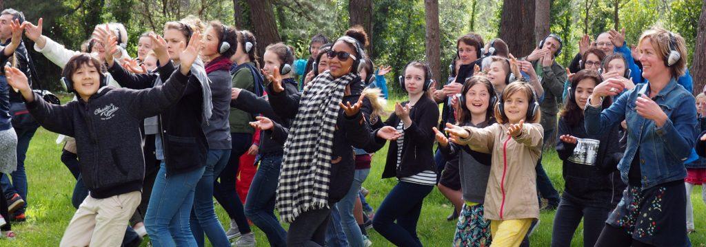 Photo représentant un groupe de personnes en train danser avec des casques sur les oreilles en pleine forêt