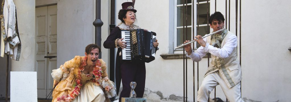 Photo représentant un homme qui joue de la flûte traversière accompagné d'un accordéoniste et d'une soprano