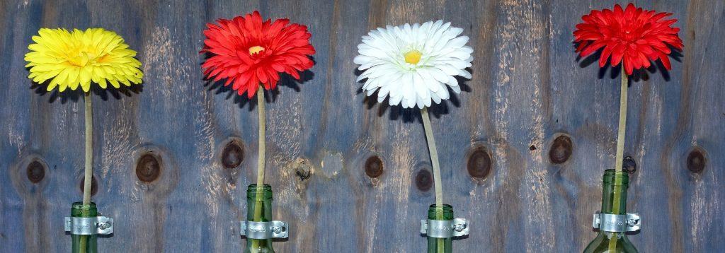 Photo représentant des fleurs en vase sur un fond en bois