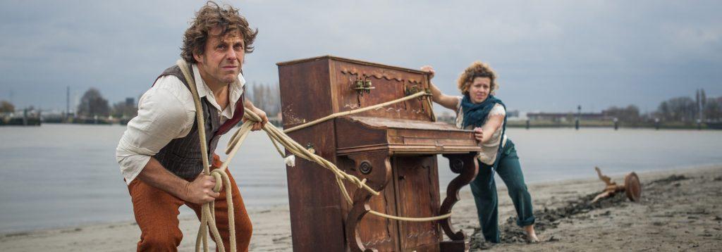 Photo représentant un homme et une femme tirant un piano sur une plage
