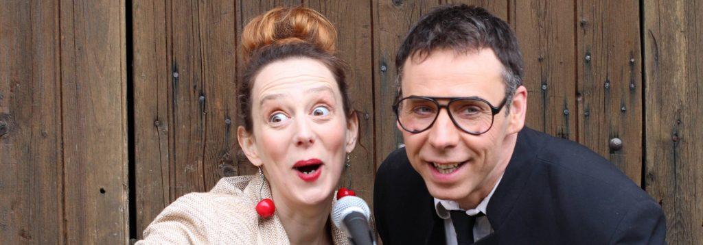 Photo représentant un homme et une femme s'adressant au public en souriant