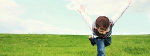 Photo d'un enfant dans un champs essayant de voler